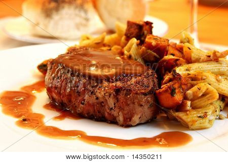 Filet Mignon beef steak with pasta vegetable salad.