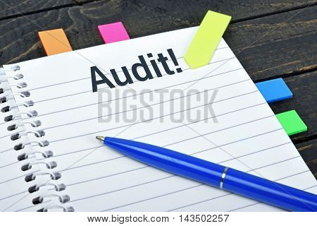 Audit word on notepad and pen