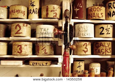 Old workshop with rusty tins of nails, screws, etc, with vintage hand drill.  My dad's shed.