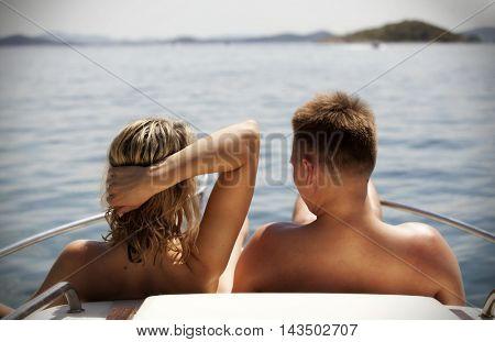 Man and woman enjoying vacation on a sailing boat watching the sea