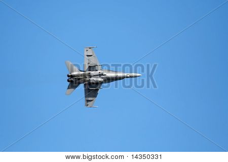 F-18 fighter jet, in flight against brilliant blue sky.