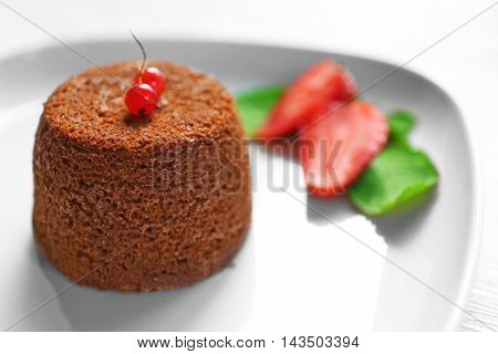 Tasty chocolate fondant with red currant and strawberry on white plate, closeup