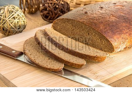 Sliced homemade dark rye oblong bread and knife on wooden cutting board.