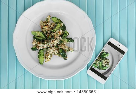 Salad with smartphone on table. Food blog concept