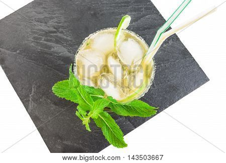 Black serving slate platter with glass of mojito cocktail isolated over white background. Top view.