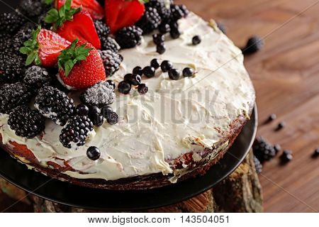 Appetizing cake decorated with berries on wooden background