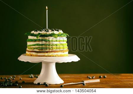 Delicious cake on stand on dark green background