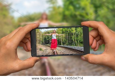 Woman hands with mobile cell phone to take a photo of young lady in red dress walking on railway tracks