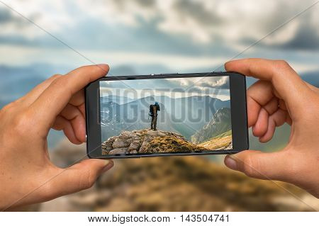 Woman hands with mobile cell phone to take a photo of young man standing on a rock and looking at a beautiful mountains