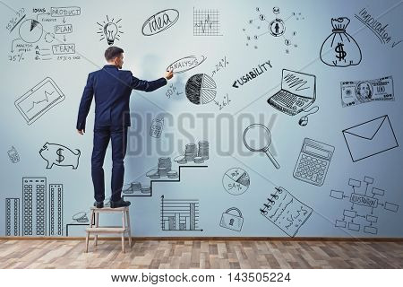 Businessman drawing plan on blue wall. Business project concept.