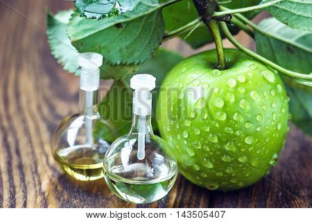Apple vinegar in glass jar with ripe dreen fruit. Bottle of apple organic vinegar on wooden background. Healthy organic food.