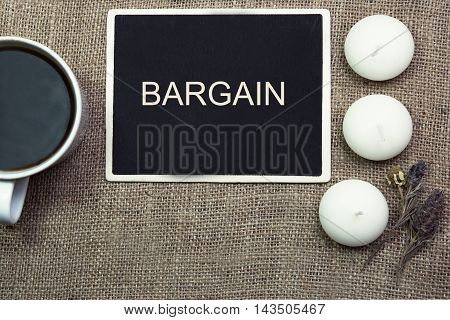 sentence BARGAIN written with chalk on a blackboard, on a table with pen.coffee and coffee cup.