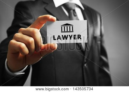 Handsome businessman holding business card LAWYER close up