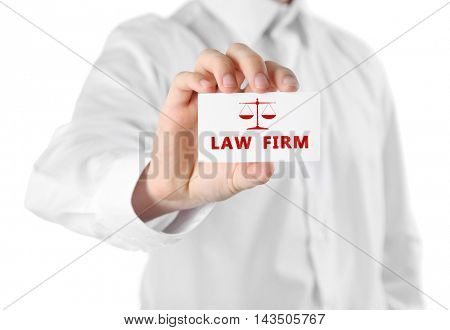 Handsome businessman holding business card LAW FIRM close up