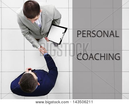 Personal coaching concept. Two businessmen shaking hands on grey background