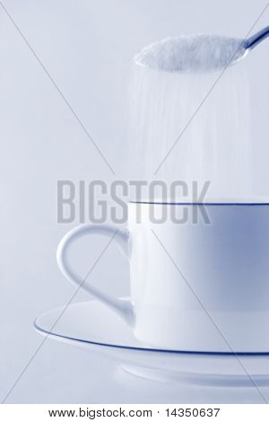 Sugar cascading from a spoon into a coffee cup.  Business concept - sweetening the deal!