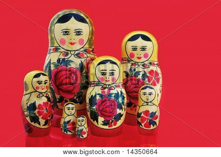 A family of Russian babushka nesting dolls, on a vibrant red background.