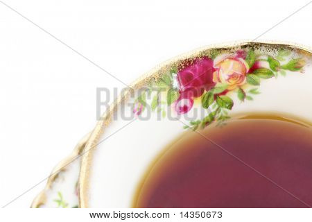 A cup of black tea in a classic, gold-rimmed floral china teacup.