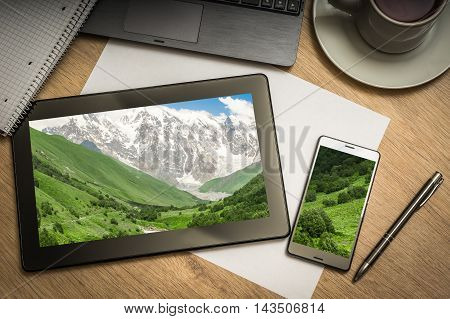 Digital tablet on business table with snow-capped mountains in Georgia on screen and mobile phone paper pen laptop and cup of coffee - above view