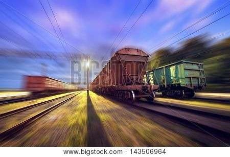 Railway Station With Cargo Wagons In Motion At Night.