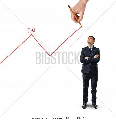 Businessman stands with folded arms looking upwards at big hand drawing rising diagram isolated on white background. Succesful management. Supervision and control. Investment and finance.