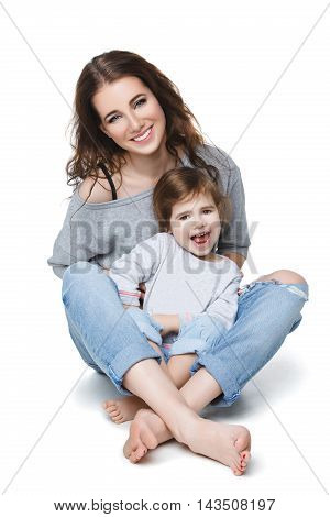 Beautiful young woman with little girl. Mother and daughter isolated over white background. Copy space.
