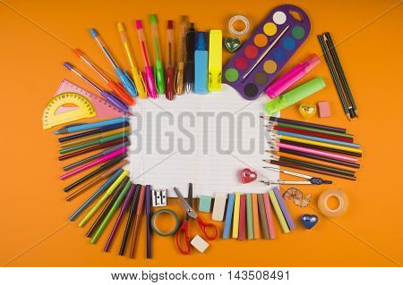 Different colorful school supplies on notebook on orange background.