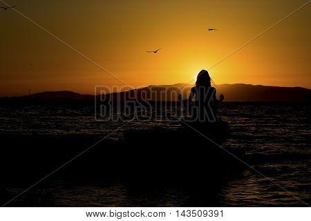 Young model doing yoga on seaside at sunrise