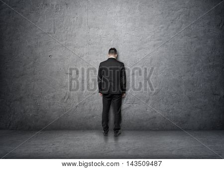 Back view of a businessman with bowed head standing in front of a concrete wall. Problems and doubts. Business staff. Ideas and concepts.