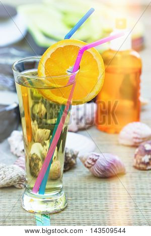 Concept of relaxing on the beach - refreshing drink and sun protection