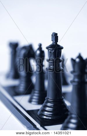 Chess, with focus on the king.  Very shallow depth of field.  Blue duotone.