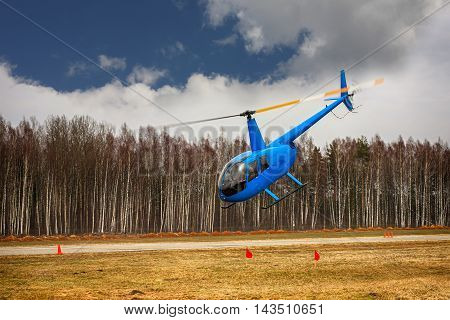 The aircraft - the small blue helicopter at competitions makes flight at low height on cloudy sky background.
