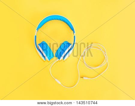 Blue Headphones Lie On A Colorful Yellow Background