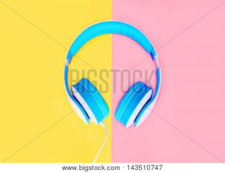 Blue Headphones Over Colorful Yellow Pink Background Top View