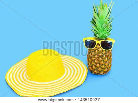 Pineapple With Sunglasses And Yellow Straw Beach Hat On Blue Background