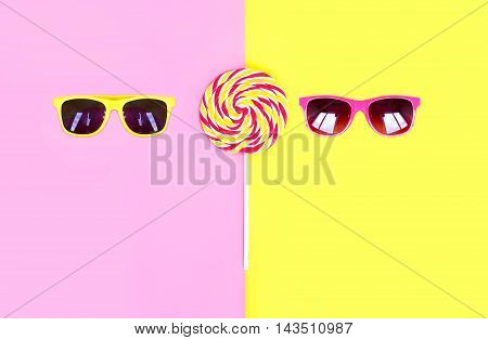 Two Sunglasses And Colorful Lollipop Caramel On Stick Over Pink Yellow Background Top View