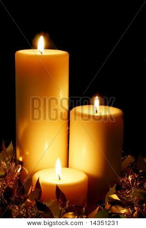 A trio of golden Christmas candles, with black background.