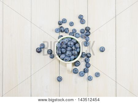 Mug filled with blueberries on a white wooden background.