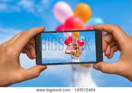Woman hands with mobile cell phone to take a photo of happy young lady celebrates birthday and playing with balloons
