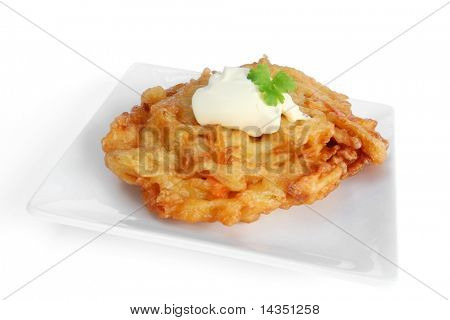 Potato pancake or latke, with sour cream, on a white plate.