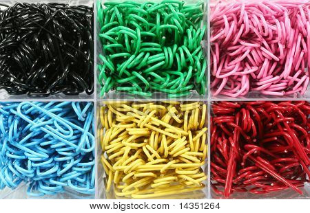 Box of colorful paperclips, each color in its own compartment.  Closeup view.