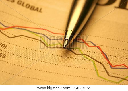 A silver and gold ballpoint on a newspaper stock market graph.