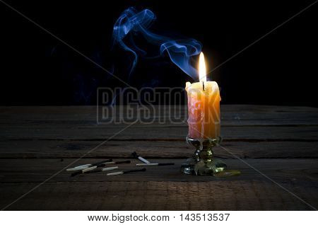 Burning candle smoke and burnt matches on a wooden table.