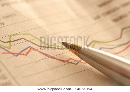 Ballpoint on newspaper stock chart, in ambient light.