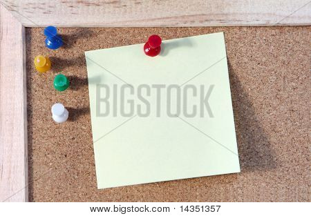 Blank yellow note on a corkboard, with pushpins.
