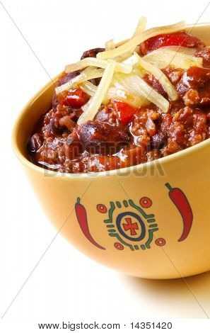 Bowl of chili with peppers and beans, topped with grated cheese.