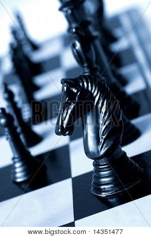 Black knight on a chessboard, in blue duotone.  Shallow depth of field.