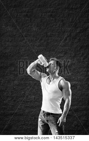 young man with strong muscles water drink after training -- black and white stylized photo