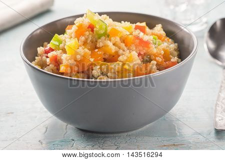 Close up of colorful quinoa salad on blue vintage wooden table