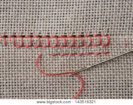 Fragment of embroidery on the canvas with a needle